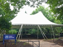 A large event tent set up over a brick path surrounded by trees at the Smithsonian's National Zoo's Great Meadow
