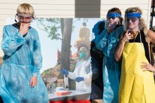 Students posing wearing protective clothing wildlife scientists studying zoonotic diseases wear in the field.