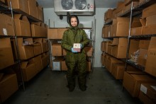 A nutrition lab research assistant at the Zoo wearing a full-body snowsuit stands in the freezer where animal milk samples are stored. The shelves are stacked with cardboard boxes and she holds a small box filled with tubes of milk samples.