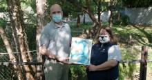 Giant panda keepers Marty Dearie and Nicole MacCorkle hold a painting created by giant panda Tian Tian to reveal that the sex of the giant panda cub is male.