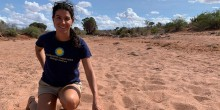 Francesca Vitali takes a knee in a sandy area of Kenya. She's wearing a navy Smithsonian Conservation Biology Institute shirt and is pointing to wildlife footprints in the sand.