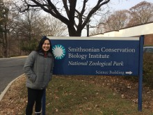 An intern with the Smithsonian Migratory Bird Center poses for a photo next to the sign for the Smithsonian Conservation Biology Institute's Science Building