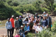 A group of George Mason University undergrad students pose for a photo in the field in Kenya