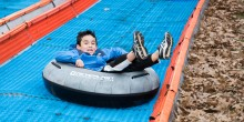 Child on snowless tubing track