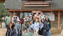 A group of George Mason University students pose in front of a Mount Kenya National Park World Heritage Area building
