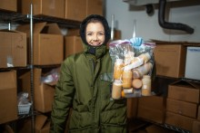A nutrition lab research assistant at the Zoo wearing a full-body snowsuit stands in the freezer where animal milk samples are stored. She holds a bag full of milk samples, and is surrounded by shelves stacked with cardboard boxes full of more samples.