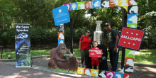 two adults and a young boy pose in front of the Stanley Cup on display at the Zoo