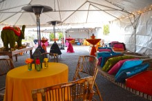 A colorful catered event set up under a large tent with cocktail tables, benches with pillows and lights