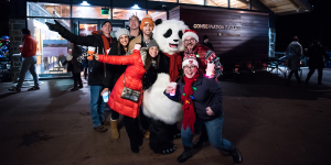 "A group of smiling young men and women dressed in winter clothing pose for a photo with ""Panda Pal"" the Zoo mascot during BrewLights, a holiday craft beer event"