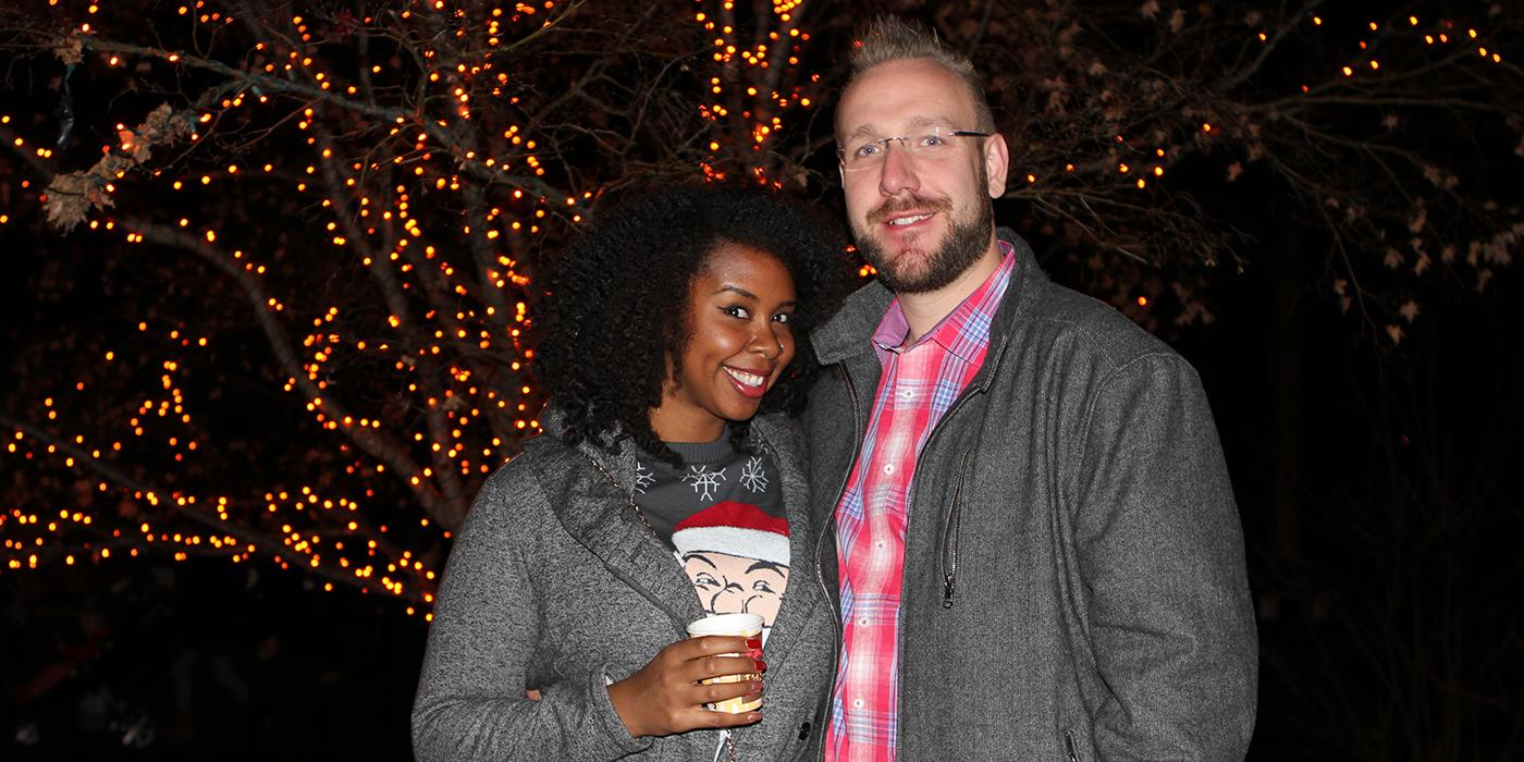 a couple stands in front of twinkly lights holding a beverage