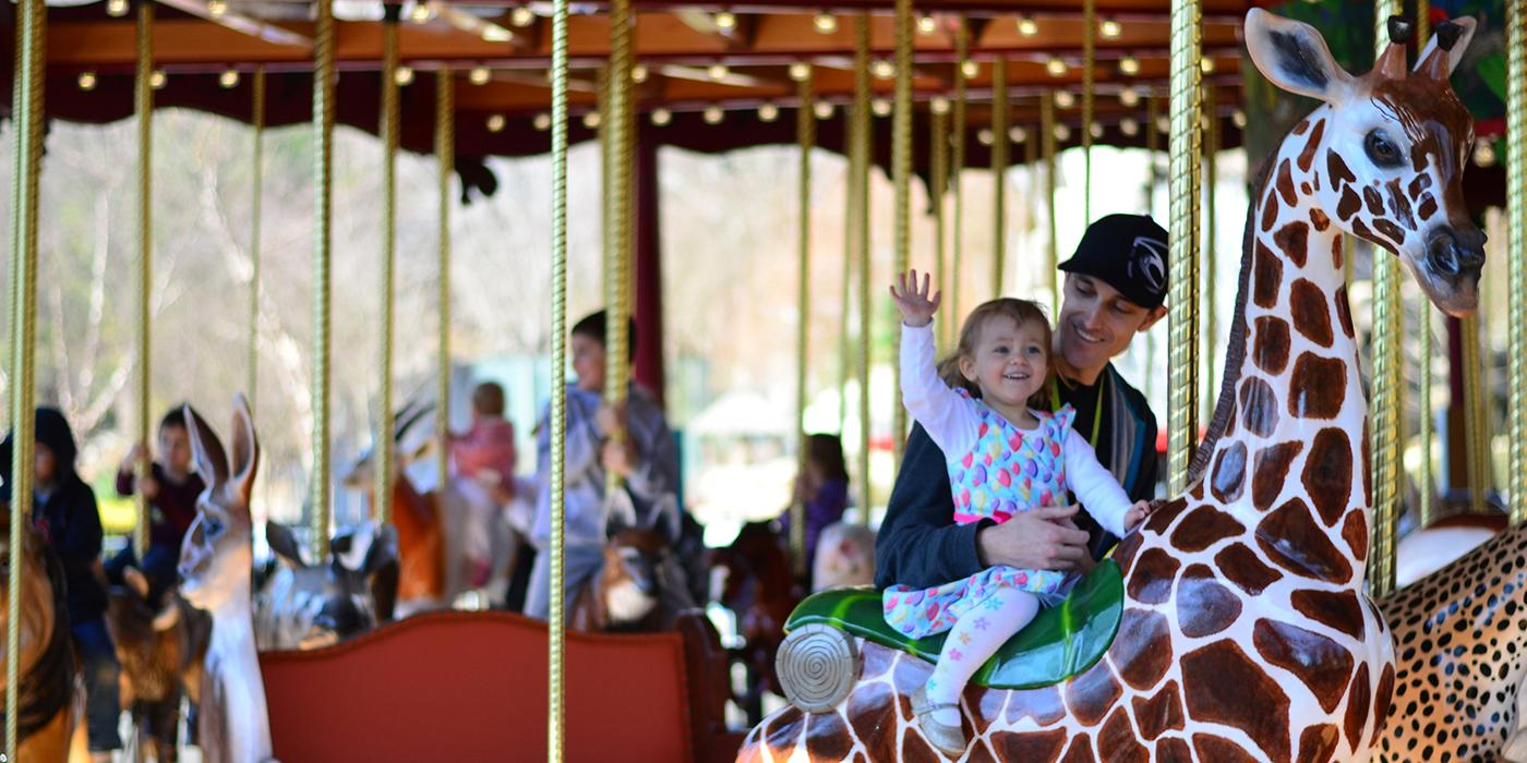a little girl waves as she rides the carouse