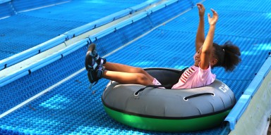 a little girl sits in an inflatable tube as it slides down a blue rubber track