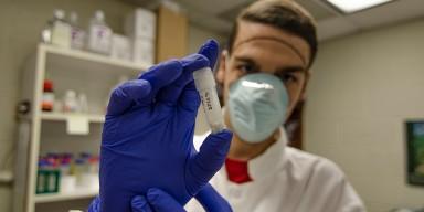 scientist holding up vial of ancient bones