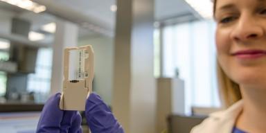 female scientist holding up slide