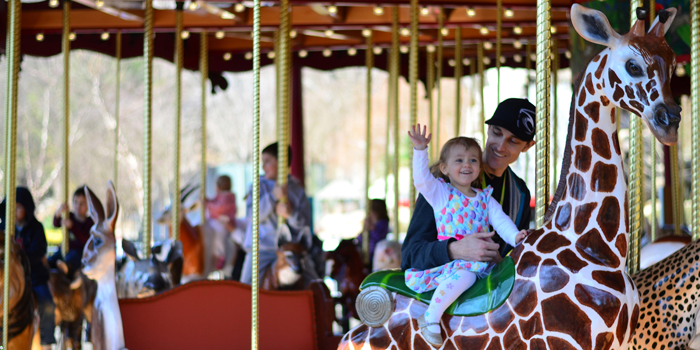 Visitors ride the Zoo's carousel. In the foreground, a young girl with one hand in the air sits atop a giraffe seat while her parent holds her in place.